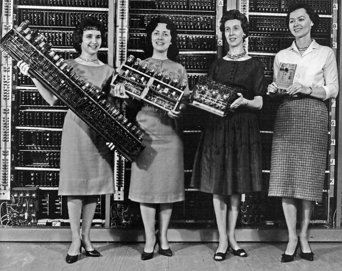 Women mathematicians and programmers holding early electronic computer modules based on vacuum tubes
