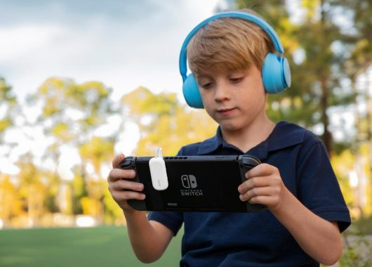 A boy using headphones while playing with a device (From newatlas.com)