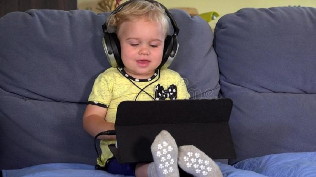 Toddler watching something on IPAD wIth headphones (from dreamstime.com)